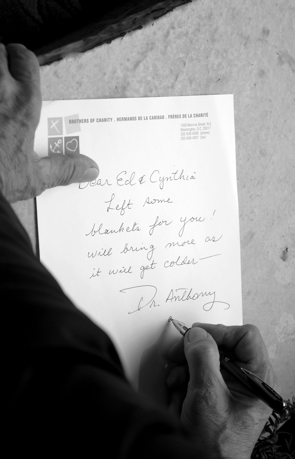 "Dr. Anthony Martinez writes a note for Ed and Cynthia, the homeless couple who live outside the Holy Redeemer Catholic School. ""Dear Ed & Cynthia,"" the note says. ""Left some blankets for you! Will bring more as it will get colder — Dr. Anthony."""