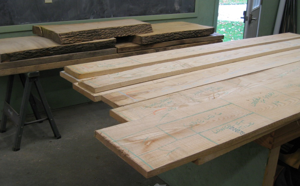 Breaking it down: the 4/4 boards will be the benches; big boards in the background willbecome the trestle table base