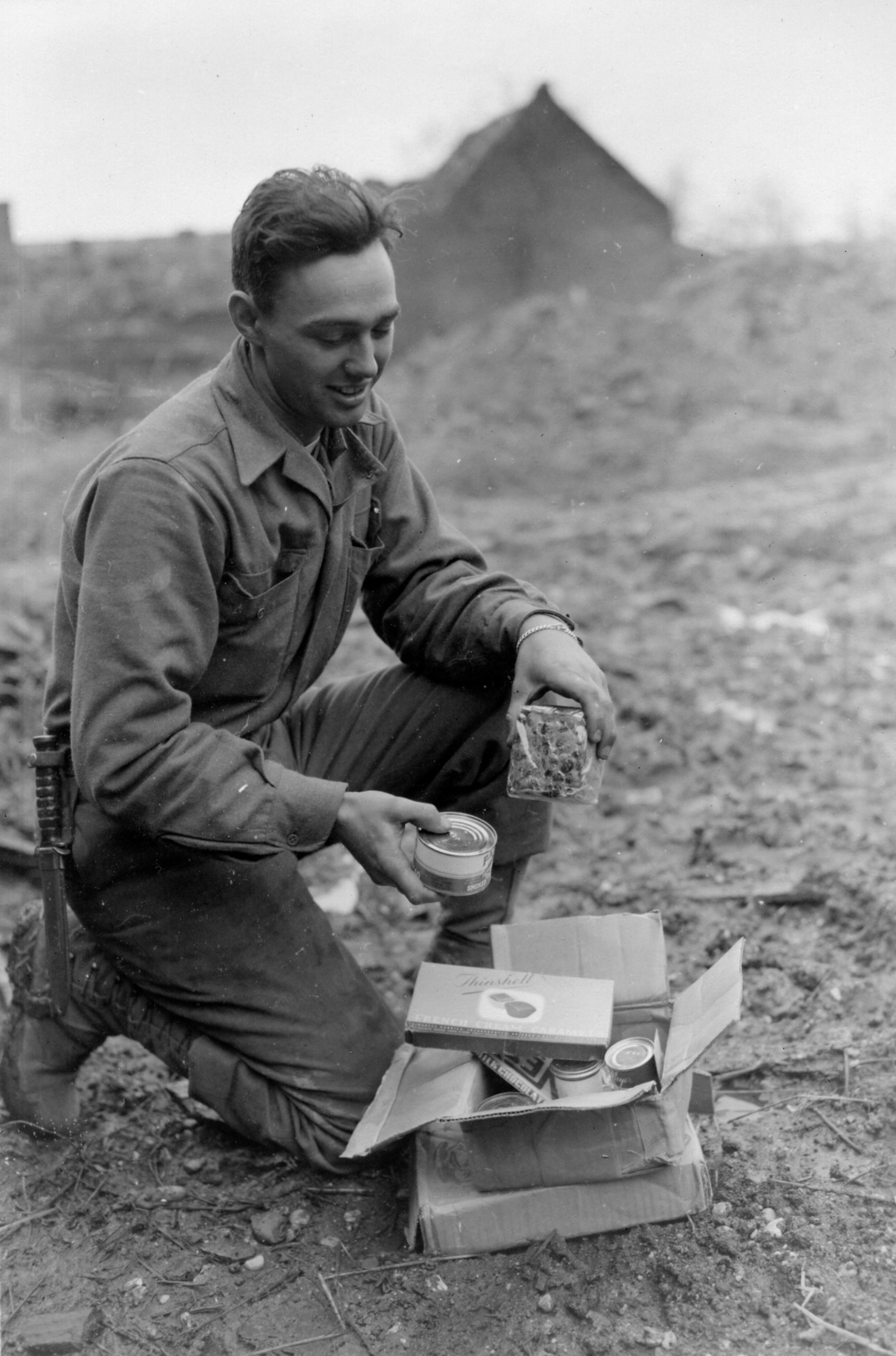 Dec 1944.  GI from Chicago opens a holiday package from home.