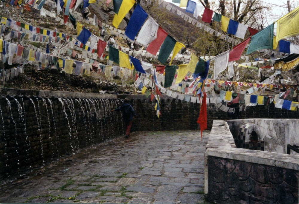 Tibetan prayer flags flying above a mountainside fountain.