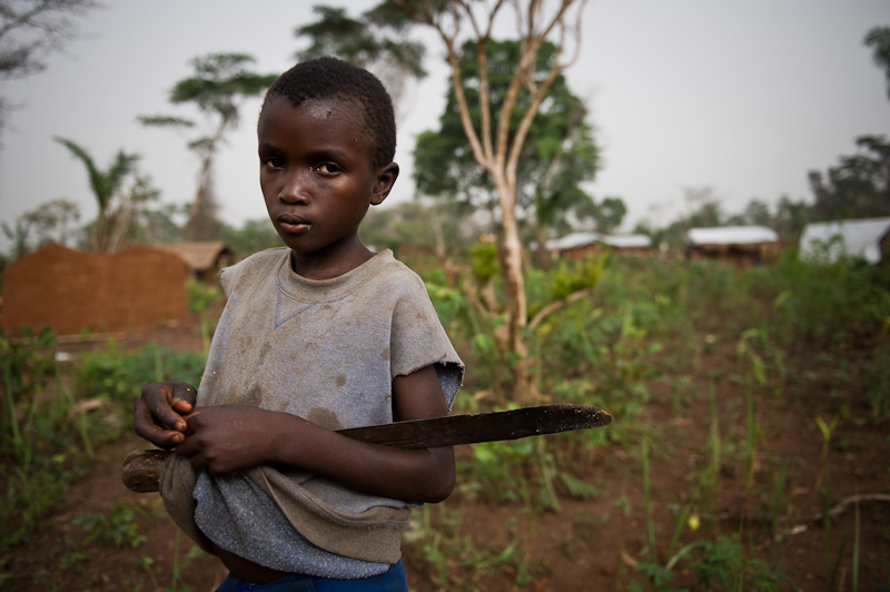 A young boy stands with a  panga , used for chopping small trees for firewood and making homes, in the Nanzawa camp for internally displaced persons on the outskirts of Dungu in D. R. Congo's Orientale Province.  Lord's Resistance Army rebels, led by Joseph Kony, have been attacking civilian populations in Haut and Bas Uélé districts since 2008, resulting in the displacement of over 300,000 people, according to an international NGO working in the region.