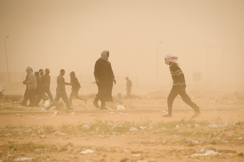 Chadian men walk through a sandstorm that engulfed the region around the Egyptian border near Sallum on March 31, where an estimated 2500 people are still stranded, having fled the Libyan revolution. Many of those at the border are sleeping outside under blankets and make-shift shelters, the Egyptian authorities refusing to allow even any semi-permanent structures, such as tents.    For me, this would be my final day working at the border. This last trip would cost me my left eye for a few days. An infection would seal it shut for a week. But I had an out. A comfortable bed in Khartoum, and then Cairo. Clean water and time for repose. For the thousands stranded at the border, right now, there is no end in sight. And no sign of an end to the fighting raging in Libya.