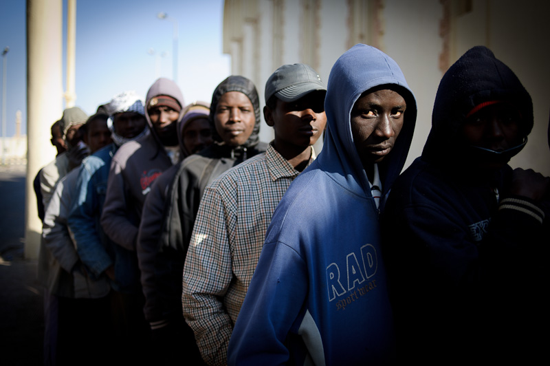 A group of Chadian men queue at the Egyptian border at Sallum having fled the escalating conflict in Libya. These men had left their country to find work and stability in their northern neighbour, but now find themselves stranded at the border without any proper accommodation. They are waiting to regularise their papers in order to be able to return home to Chad. In the meantime, cardboard roofs offer their only shelter.