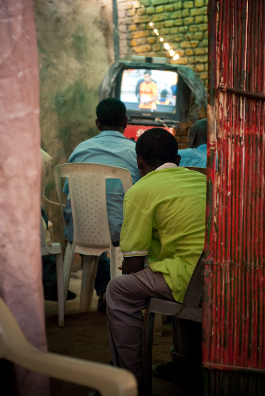 The African World Cup The rhetoric all over Africa was that it was their World Cup, South Africa would be sharing it with the entire continent. Cafés and restaurants over Khartoum were filled with men watching screens, ranging from Sudanese men clad in their traditional djellaba puffing on narghile, to shirt-wearing Westerners, ummm, also puffing on narghile. With alcohol illegal in the country, what would have been a very pleasant beer was replaced with fruit juices and thick, warm sahleb. Everywhere was broadcasting the matches. In the small grocers next to my house, the owner was huddled behind the counter, straining to hear the commentary issuing from his radio. Cultural centres screened their countries' matches, as did the embassies. The folk of Sudan Boombox organised an event on the street in front of the Dutch embassy, a giant screen next to the stage where DJs were spinning hip-hop. People danced in the street, one eye on the screen, the other on the MC — I checked my self, was I still in Sudan? The Dutch ambassador took to stage, inviting everybody back if his team made it through. (They did, but there was no follow-up event.) I watched games in the dust-floored back room of an Ethiopian restaurant, the rooftop of an Egyptian café, the opulent courtyard of a Sudanese establishment. The cries of one particular Arab commentator become a running joke. As friends headed over to the most western-leaning café in town for the final, I joined some others in a smoke-filled room of a local shisha joint, as the waiters squeezed through the crowd carrying baskets of hot coals, waves of heat passing through the already baking room. When Spain scored, the men in white behind me were on their feet, dancing. It may not have been their country's team, but their love of FC Barcelona or Real Madrid took precedence. The amjad driver who picked us up afterwards had a big grin. He, too, was rooting for Spain, and outside in the dusty streets of the capital, he had sat, hunched over his radio. Khartoum nights often offered little in the way of activity, but for that month of the tournament, the city felt alive.
