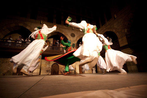 Sufi Dancing @ Cairo    The Al-Tannoura Traditional Troup perform a few times per week at the Wekalet El-Ghouri Arts Centre, near Khan al-Khalili.    Sufism is where mysticism meets Islam. The basis of this dancing is to separate the mind from the body through the repetition of movement, to become closer to God. Or at least that's how it was explained to me. I'm not sure how far removed they really become on stage, dancing with strict coordination as the live  musicians  provide the rhythm to which their movements anchor, but in any case, it's quite the show.    Entrance is free if you're in town.
