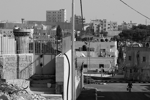 "Aida Camp    The dominating  watch-towers  built into the side of the  West Bank barrier  look-out over a piece of waste-ground. Streaks of red-paint run down the side of them, like blood running down grey concrete skin. On the hill opposite stands a mass of two-storey concrete houses — the Aida refugee camp — living under the shadow of the winding walls of this barrier of segregation. The camp was established in 1950 by the  United Nations Relief & Works Agency  (UNRWA) to cope with Palestinians fleeing from the newly-created Israeli state.    Across this waste-land walked Muhammad-Ali, a 48 year-old Palestinian who lives in the camp. He explains that last year, on this piece of land, four children playing here were shot by Israeli soldiers from the watch-tower. The image of the paint running down them suddenly represents the bloody repression which is issued from within their walls.    We walk across to Muhammad's house in the camp as he explains that soldiers regularly leave their concrete enclosure at night, coming into the camps at two or three o' clock in the morning, hammering on doors. They force people out into the street — children are crying as they are made to stand outside in the cold & the rain — and their houses are searched. The lump on his 76 year-old mother's wrist is a reminder of the night, seven years ago, when she was thrown to the ground, breaking her wrist. She still has pain in her shoulder. People here are scared every night when they go to bed.    The camp is severely overcrowded — in 2006 it was estimated to have a population of 3,260 refugees, covering an area of 0.71 square kilometres — although it has not been able to expand significantly since its creation sixty years ago. The buildings are limited to two-storeys. Thirty-one people live in the three rooms of Muhammad's family's house.    In the summer, there are shortages of water, and the sewage and water networks in the camp are poor. There is no ground on which they can grow food, yet the on other side of the wall I can see open hillsides rolling below the Israeli settlements.    Unemployment is also a major problem. The UNRWA quotes unemployment at 43%, and is ""affected by the increased inaccessibility of the Israeli labour market"". Muhammad explains that he used to work as a mechanic, but with the creation of the wall, he lost his job as he could not travel there. The UNRWA try to provide some employment — such as street-cleaning — but there are not enough jobs. Once you sign-up, it may be possible to work for one, two or three months in a year, but this is all. He would like just a small amount of money with which he could start a shop, selling fruit & vegetables, but right now, it is hard enough finding money to buy food for his family.    Despite the hardship that they face, his family were incredibly friendly, welcoming and hospitable. As they served tea, and sent-out a child in search of biscuits, I felt incredibly guilty taking the food of these people who struggle for their daily existence. But trying to refuse offers of food and drink in Arab cultures is impossible. Offering money to them is offensive.    Back in the hostel that night, people would ask ""have you had a nice day"". I didn't know how to reply."