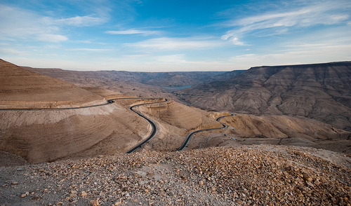 "The Road to Wadi Mujib The notion of going to where you can get to, rather than finding a way to get to where you want to go, is a luxury rarely afforded back home. I had wanted to get to Dana, but on a Friday — the Muslim day of rest — there were no buses going that way. When I then asked ""where can I get to today?"", the question seemed lost on the locals and I was just told to go back to Amman to get other buses from there. Taxis offered the ride at an exorbitant rate. I noticed ""Dhiban"" written in Arabic on the side of a bus that was slowly filling up with people. The map showed that it lies on the northern edge of Wadi Mujib, Jordan's ""Grand Canyon"", and in vaguely the right direction. That would do. This change of plan meant a new acquaintance in a bus rarely used to seeing foreigners; after a phone call to his wife back home, extra places were being prepared for lunch in a little village somewhere north of Dhiban. The lift back to the town that afternoon was in his friend's mini-van, filled with veiled women who giggled away in the back on their way to a wedding. ""You cannot look at them"", our driver told me as they spoke to me. The umpteenth cultural lesson of that day. Walking down the winding road into the wadi (""valley"" in Arabic) evening was beginning to draw in, and passing drivers warned of the danger in the valley bottom at night. The ""wolves"" they had warned of were avoided thanks to four retired men, dressed in full Jordanian garb, who stopped to offer a lift as the sun was setting. A fitting end to a day of improvised traveling, and proof that where you want to go is not always the best place to be."