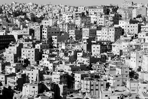 Seven Hills    I love cities built on hills. Amman's Jebel Hussein appears as a mass of haphazard grey or ochre, concrete buildings, each piled upon another. I can't help but compare it to the ordered rows of red-bricked terrace houses of Sheffield's industrial-revolution period, working class houses. A similar demographic, but a very different aesthetic.    Yet rather than being attracted to the city with the promise of  work in the factory , the people here were forced from their land in what-was-then Palestine. Push-, rather than pull-, migration, I suppose.