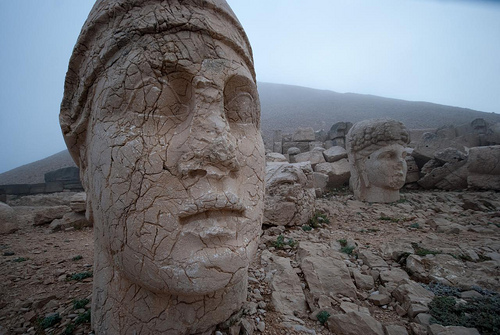 "Mount Nemrut    Nemrut Dağı is known for its temples and the carved heads of the statues of gods which now lay at the base of a funerary mound from a Commagene king of two thousand years ago. We thought it would be a nice place for a hike in the mountains.    The weather had other ideas.    After negotiating a couple of seats in a minibus to get us to the mountain from the local Tour Guide Cartel, we arrived at the visitor centre as the rain hammered down and the mountain was shrouded in cloud. The driver, and presumed head of the cartel, didn't understand why we didn't want to carry on the tour & then stay in his hotel.  ""There is nothing else to see here, and nowhere to stay, and it is going to rain for three days""  he told us.    He was right about the rain, but we managed to get a couple of beds in the dormitory beside the visitor centre, which is habited by the Turkish staff selling Kurdish trousers & miniatures of the Gods' heads to tourists.    Going out for a hike was off for the day: it was cold, we were already soaked from having visited the temple ruins at the top of Nemrut, and visibility was down near the non-existent mark. Once all the tour-groups had left, there was only Tony & I, with the six guys who occupied this brick shack, its blankets reeking of stale smoke. The evening was spent trying to understand the rules of  tavla , which they played with wild gestures and occasional strong words.    At 4.30am our alarms reminded us of our cold surroundings, and we were pulling on boots and jackets to watch the sunrise up on the mountain. The cloud was coming back after a clear night, but we did have ten minutes of unhindered sunshine before the mist rose up, producing a very eery atmosphere.    We negotiated another ride back to Kahta from a driver bringing up another group. After passing by the statues at Arsemia and its castle ruins sitting atop the cliff-face opposite, a Roman Bridge of Septimius Severus and another burial mound, we were back in Katah, catching a bus to Şanlıurfa, which swept past the lakes of the Ataturk dam project.    (More photos of  Mt Nemrut .)"