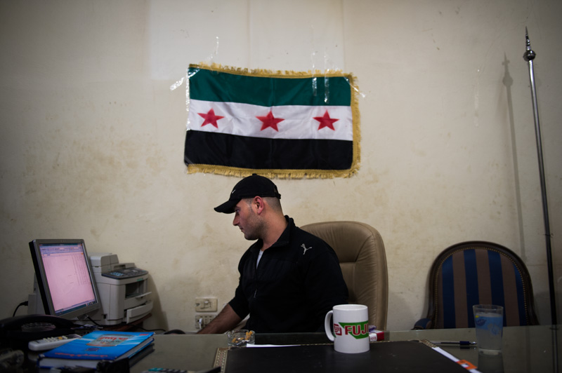 Abu Yousef sits at his desk at the Free Syrian Army controlled border at Bab al-Salama.