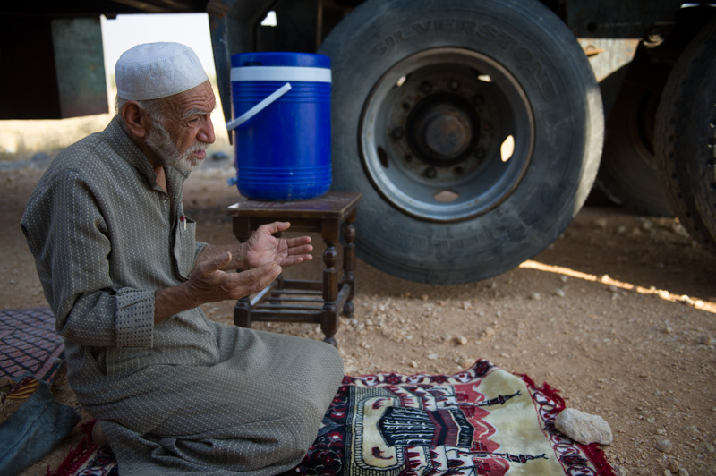 Ahmed Yassan, 73, prays on the roadside.