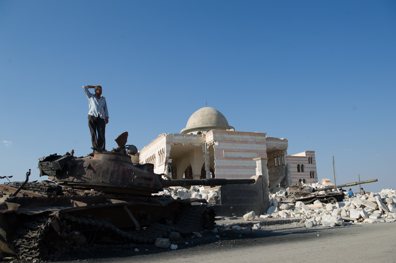 A man stands on a destroyed tank outside the ruins of a mosque damaged in fighting in Azaz