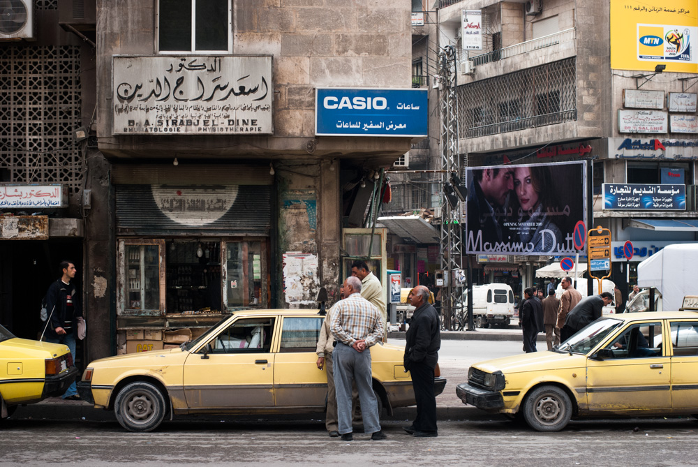 Men stand around taxis in Aleppo. November 2009.