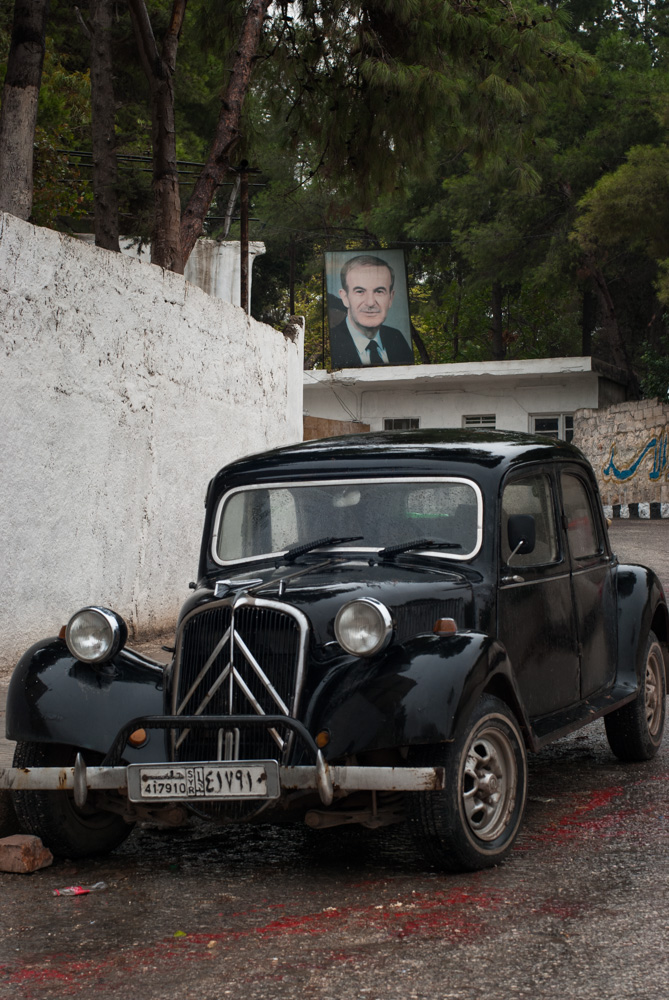 An old Citroën stands near the Aleppo Citadel, below a portrait of Hafez al-Assad, the current President's father. November 2009.