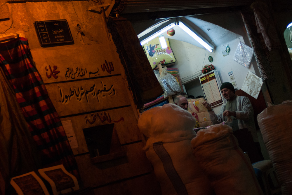 Market sellers stand in a shop at night in Aleppo. November 2009.