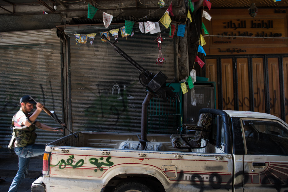 A converted pick-up truck, carrying a machine gun, is parked in a souq in Aleppo's Old City. August 2012.