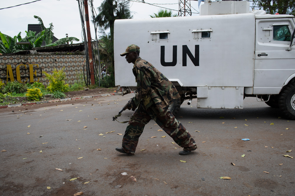 An M23 rebel walks past a UN armoured vehicle as the rebels took Goma in November 2012
