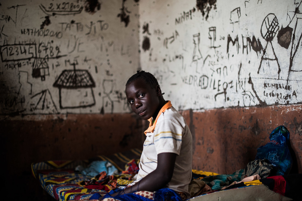 A Congolese lady sits on a bed in a dilapidated room in the Kiliwa health centre — northern D. R. Congo