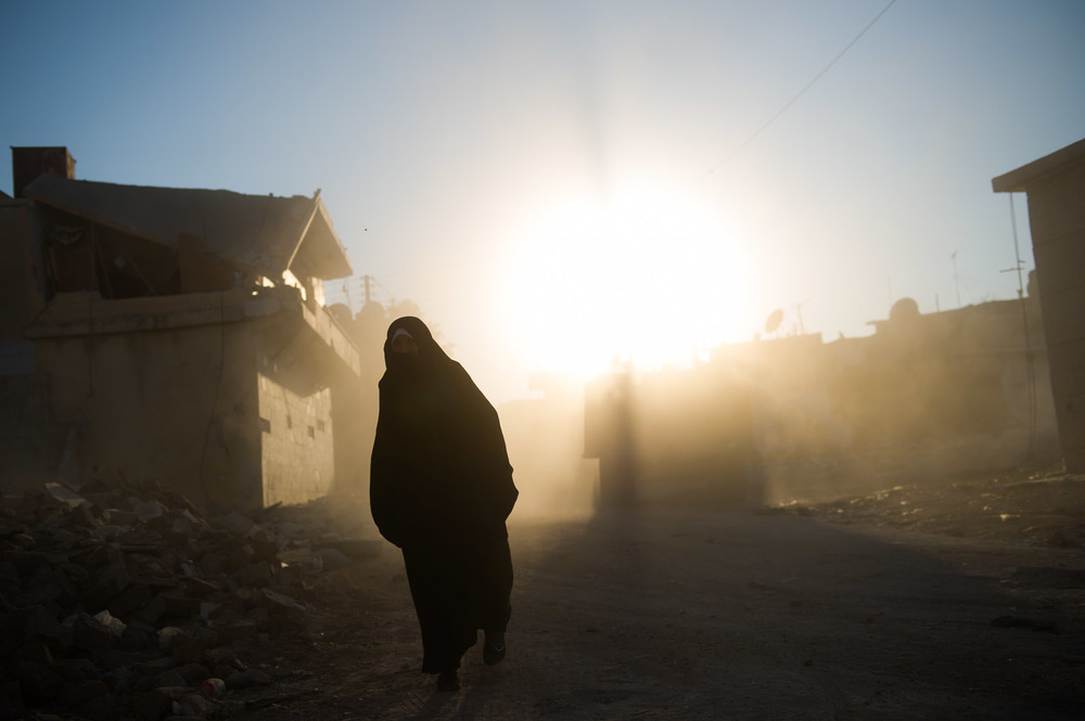 A lady walks through the dust of rubble from a bomb site. The Syrian revolution continues to be fought, as lives are destroyed.