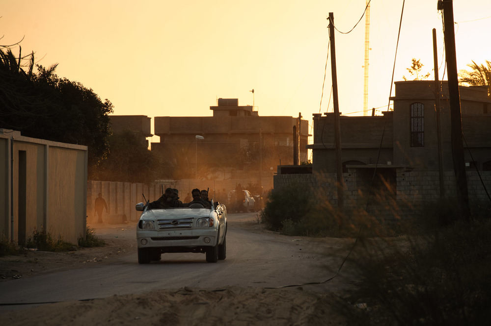 Men speed away from heavy shelling through a residential district on the edge of Misrata in a converted truck, loaded with weapons.