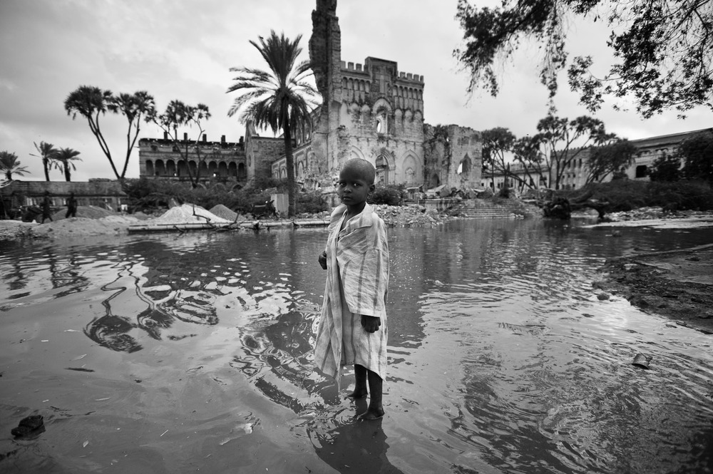 A child stands in waters following the previous night's rains outside the Viishio Governo IDP camp in Mogadishu. With the rainy season approaching, and no sanitation in the camp, water-borne diseases now become a risk in the camp -- a twisted irony of the drought they originally fled.