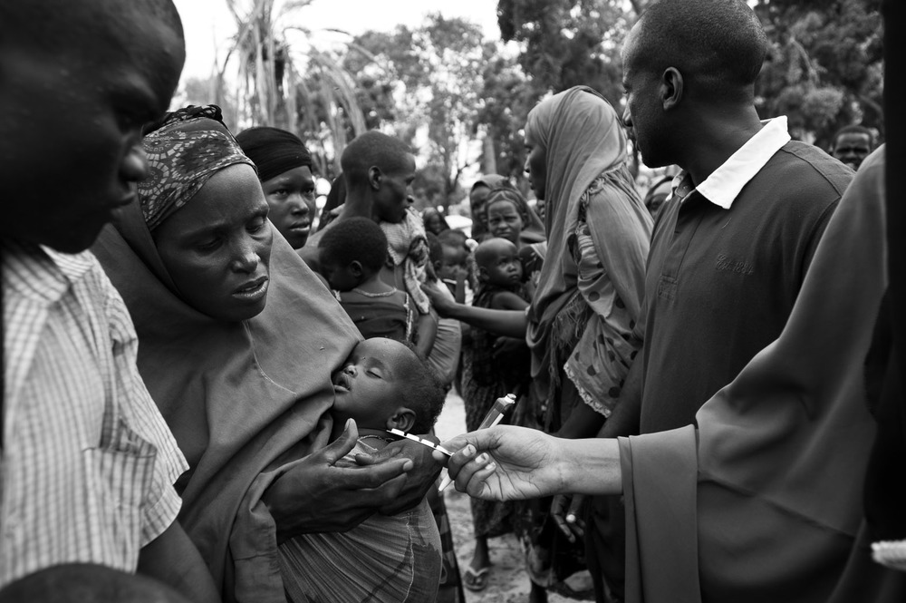 Mothers queue with their children for health care given by Concern Worldwide staff at the Viishio Governo IDP camp in Mogadishu. With no sanitation in the camp, and with little food, the health levels are dire. Staff here were distributing zinc tablets for diarrhoea, de-worming tables, pain-killers and oral rehydration solution.