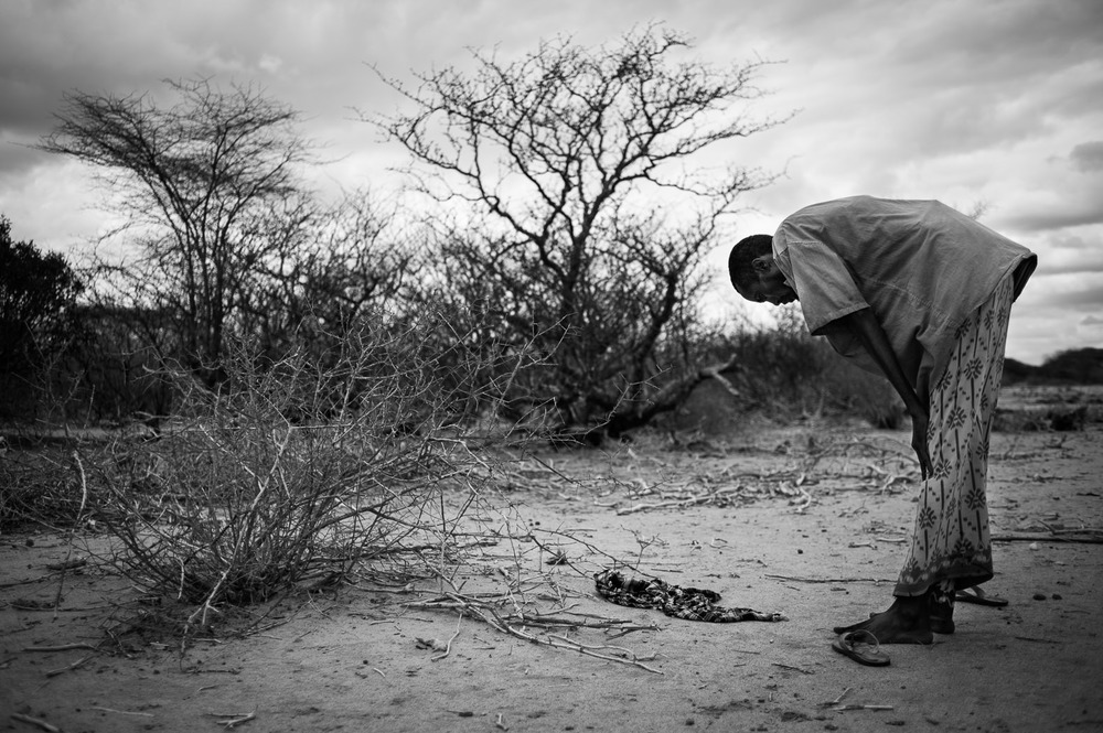 Hassan Ali prays by the road-side as he walks from the Somali-Kenyan border, just 2km away. Having walked for fifteen days with six other men, the only thing he is carrying with him is a small jug of water.