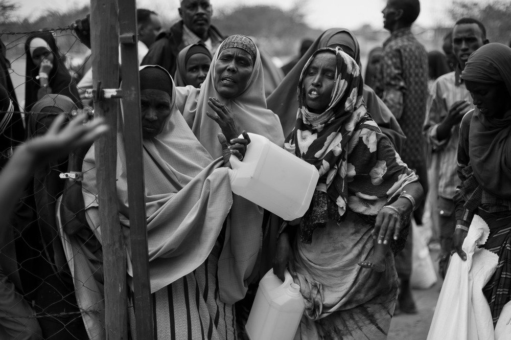 Somali women try to get access to water at the reception centre in Ifo camp. Having passed through the reception centre, refugees must wait to become registered in order to receive their ration-card and to officially assume the status of refugees. With so many new arrivals, however, there is currently a backlog of around two months, meaning that many people are without food once their initial ten-day ration has been consumed.