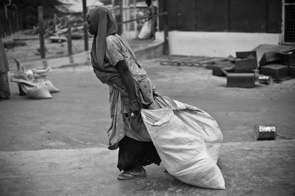 A woman drags sacks of her monthly food ration from a food distribution centre in Dagahaley Refugee Camp. Aid agencies are struggling to meet the needs of the nearly four-hundred thousand refugees now living in Dadaab, where they see around 1300 new arrivals each day. Monthly rations include flour, pulses, salt and cooking oil.