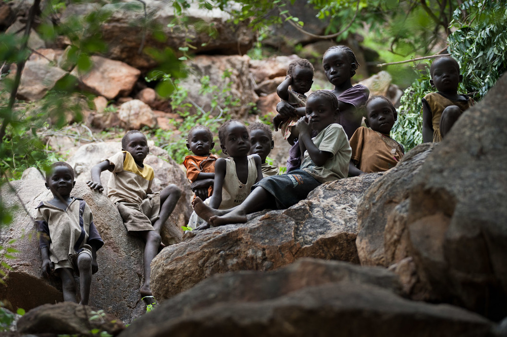 In the hills surrounding the village of Kauda, in the heart of the Nuba mountains, children spend their days hiding amidst the rocks. Their families fear the aerial bombardments and so put them here together whilst they try to work the fields.