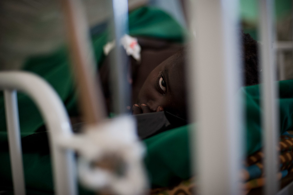 "Viviana Issa lies paralysed in a bed at a medical facility in Sudan's Nuba mountains. ""I don't know what to do with this girl"" says the only doctor in this facility. Viviana is leaking spinal fluid, and paralysed from the chest down after her spinal cord was severed by a bomb fragment hit her in the neck, breaking vertebrae. The bombing also killed two of her siblings."
