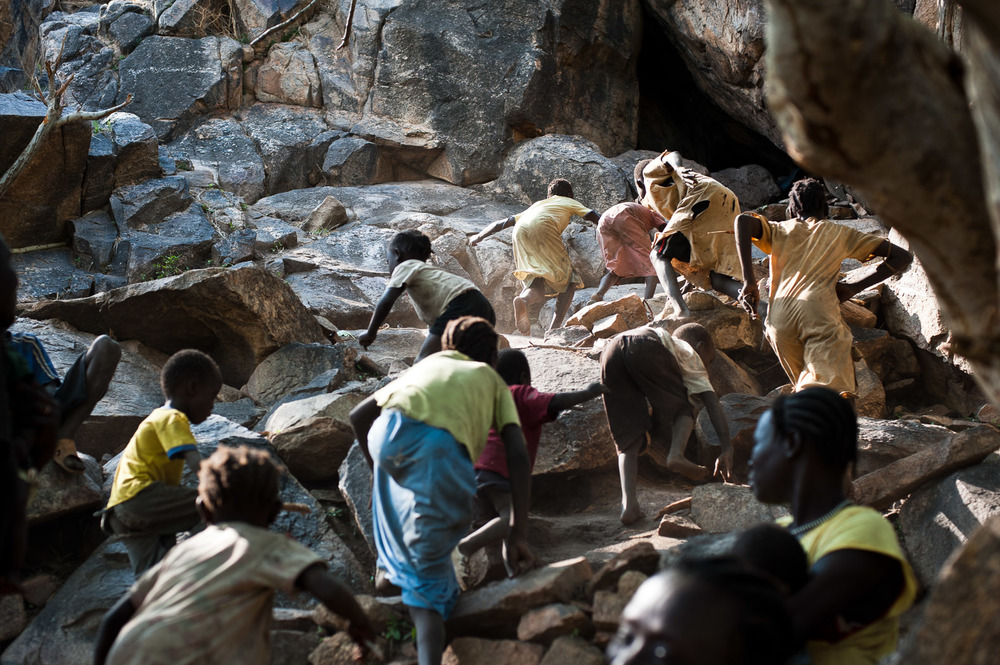 Mothers and their children flee into a cave in the hills surrounding Lwere in Sudan's Nuba monutains as an aircraft flies overhead. Hundreds of families have fled their villages, taking refuges in the hills after being terrified by frequent bombing by Sudanese Armed Forces in the region.