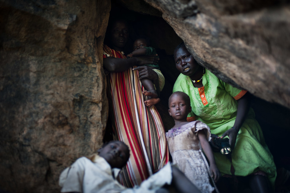 A mother looks out of a cave, terrified, as she takes shelter from an aircraft flying over the hills surrounding Lwere.
