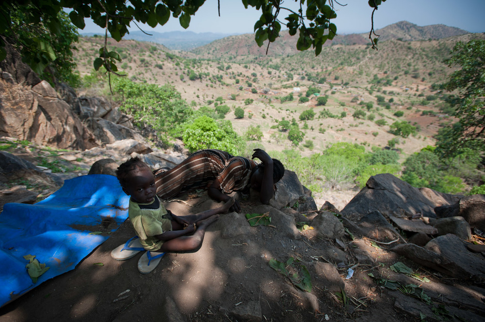 "In the hills above the compound of Abdel-Aziz Al-Hilu, many families including twenty-two year old Zuhour Bashir and her daughter Naniya (3), take shelter around some caves in the hillside. Zuhour has 3 children, and has been sheltering here for one month. Blasts and shrapnel from the bombings are visible on the walk up to these hills. ""I have seen so many Antonovs here, it is very scary. The children are all crying"" says Zuhour."
