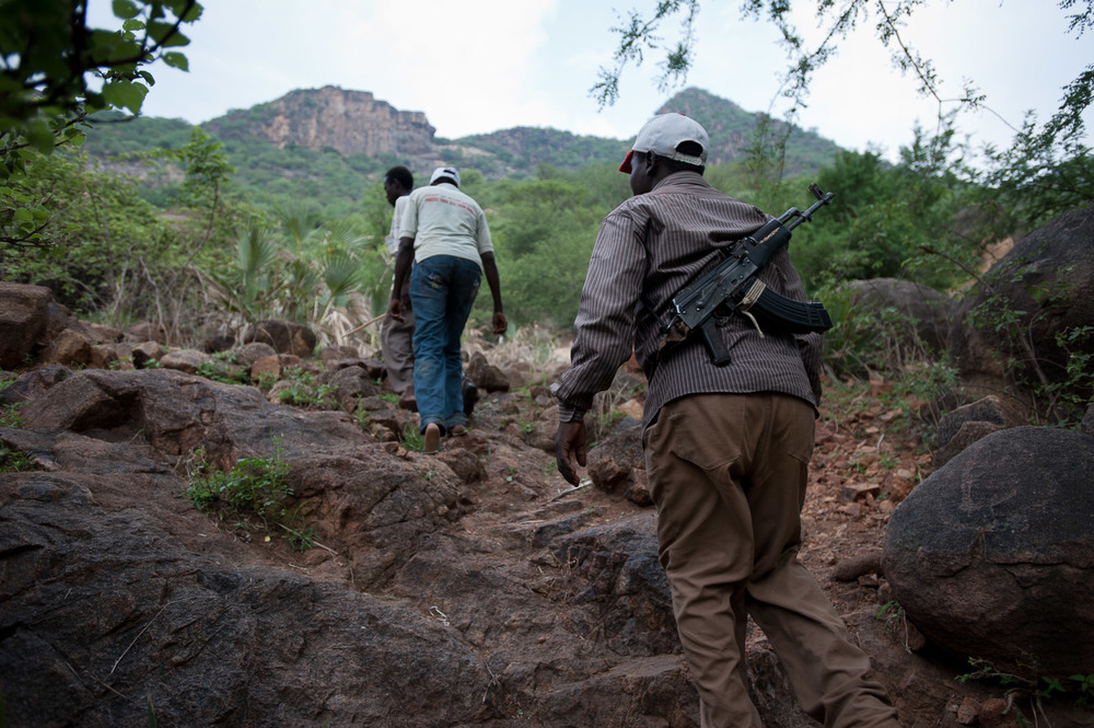 An armed Nuba, affiliated with the SPLM-North, walks up a mountainside near to Kurchi in the Nuba mountains.