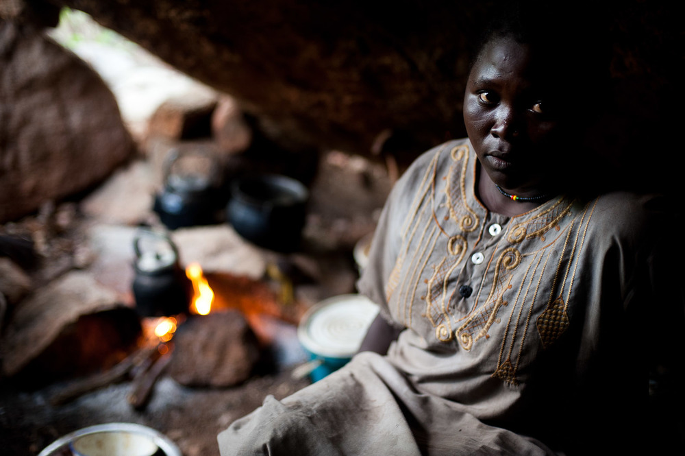 In a cave above Kurchi, a woman sits in the 'kitchen' of her group of several families, boiling water for tea.