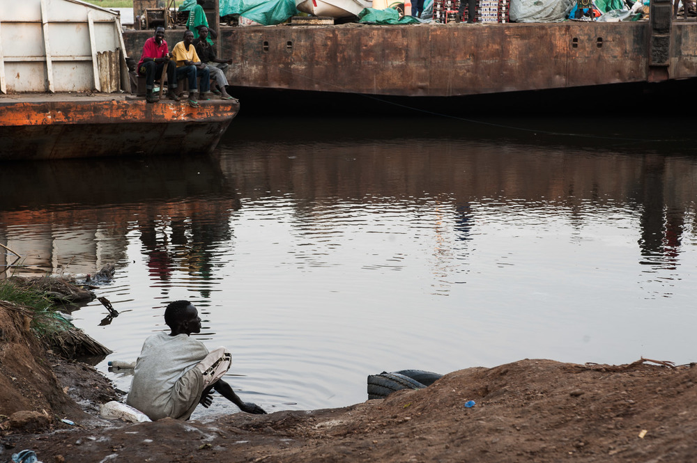 A trader from one of the many barges that plies the Nile between north and south Sudan, washes in the river at dusk.  With such a poor road network -- due to infrastructure and seasonal rains -- much of the goods transported through South Sudan, particularly from Khartoum, are shipped by the river.