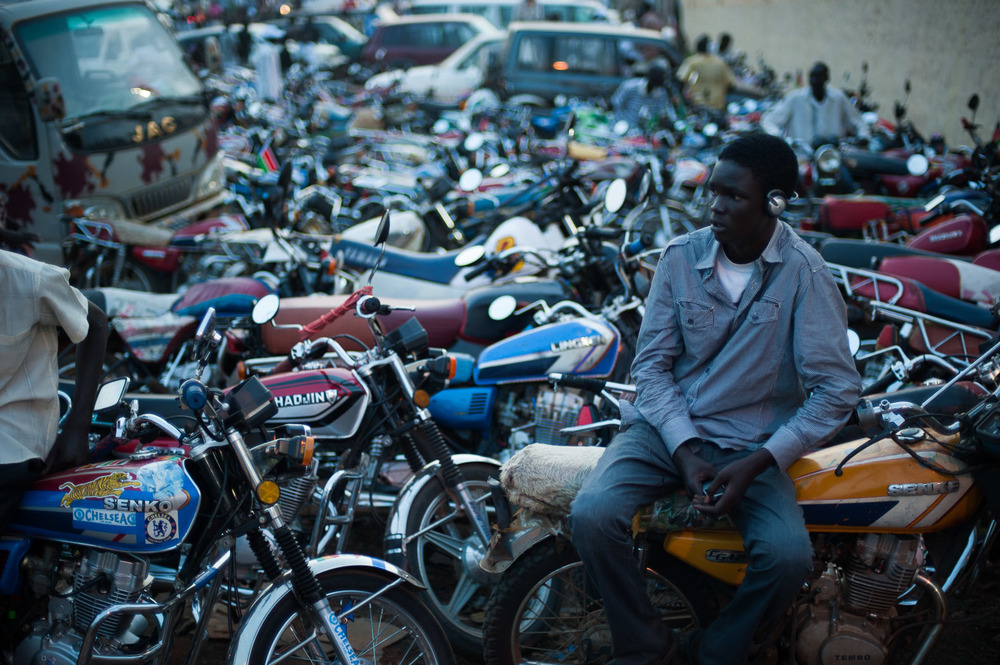 "A young ""boda boda"" (motorcycle taxi) driver sits outside the Juba stadium as South Sudan's international football team plays its first match.  The country has been flooded with affordable, Chinese motorcycles, which many people use to get around."