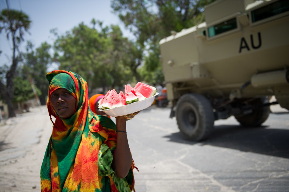 A lady sells watermelon in the streets of central Mogadishu as an African Union armoured personnel carrier passes.