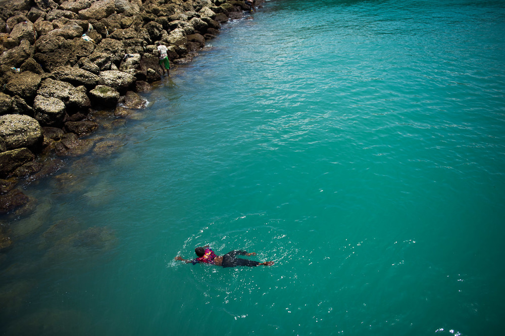 A Somali boy swims in the waters at Mogadishu's port, where tons of cargo arrive aboard large vessels.