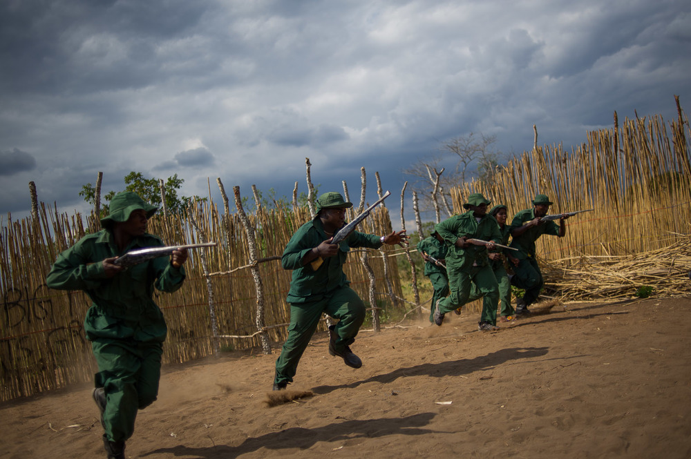 "The ""Big Power Arts Group"", acting as Wildlife Rangers, charge during a reenactment of a film they are producing, entitled ""Who is to blame?"" The film explores the illegal poaching of animals stemming from Mloka, a village notorious for elephant poaching."