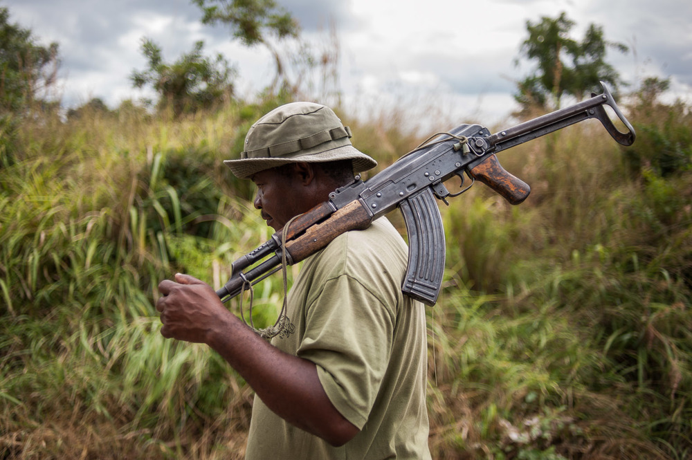 Wildlife ranger Simba Michael, walks holding his AK-47 semi-automatic rifle through the Selous Game Reserve.