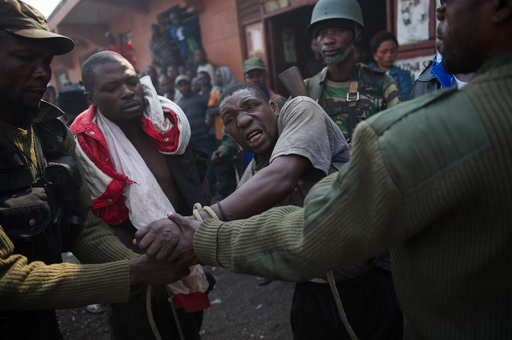 Civilian populations grew increasingly confident in denouncing the rebels. Here, a men accused of being M23 spies are taken away by Congolese army soldiers; if not for their intervention, the local population would likely have lynched the men.