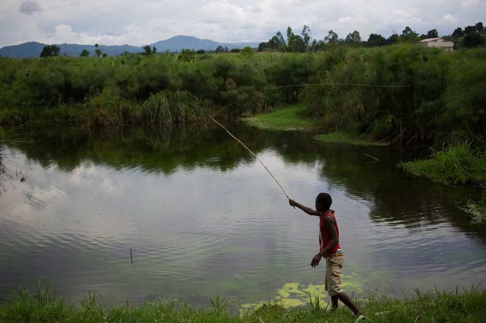 A boy fishes at a small lake on the Goma - Rutshuru road, the day after rebels pulled back and left the territory for the first time in over a year.