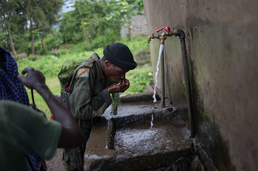 Congolese army soldiers drink water on the long walk up to Bunagana as they deploy to retake the town.