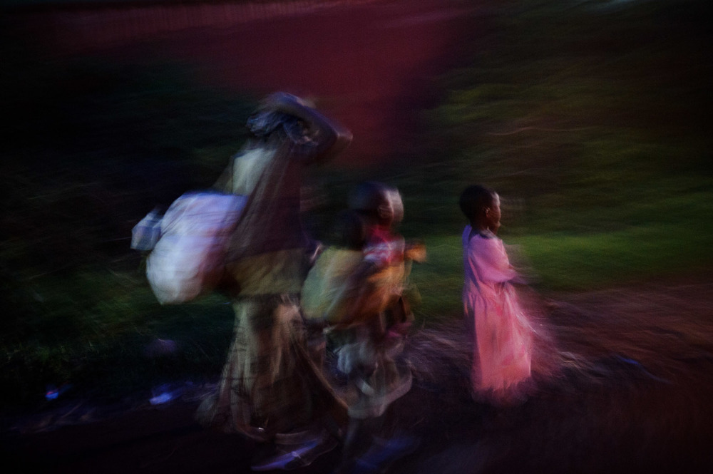 A displaced family walks towards Goma