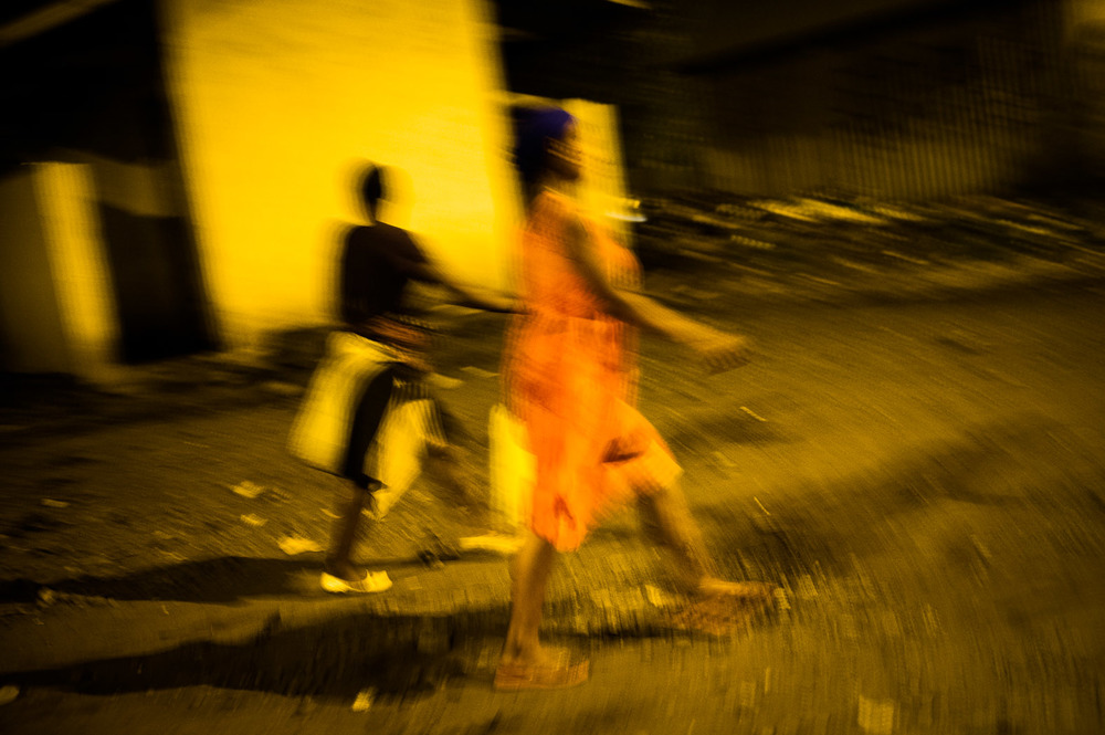 Women walk through the dark streets of Goma at night