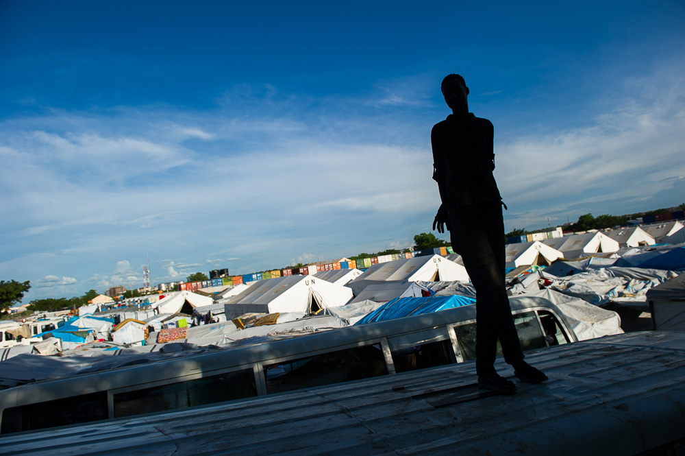 A displaced Nuer man stands overlooking the UN camp in Tong Ping.