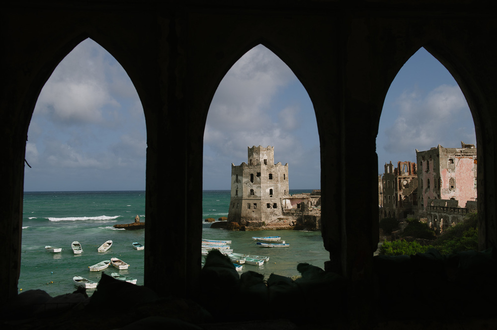 Fishing boats sit in the harbour next to Mogadishu's old lighthouse and port.