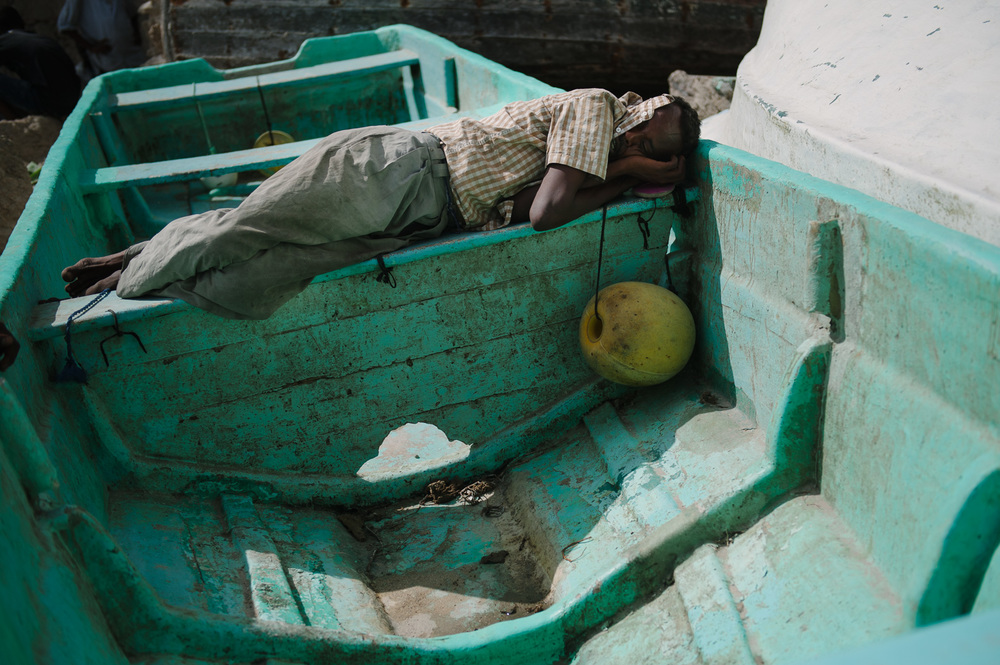 A man sleeps in an empty skiff in the boat-yard
